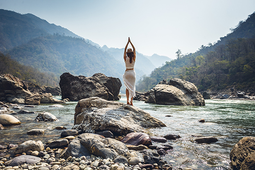 woman - practicing yoga - ganga river - Mikhail Ivannikov - Shutterstock