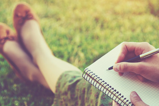 writing in notebook - stock image - Ivan Kruk - Shutterstock